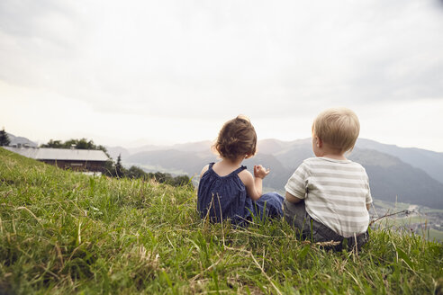 Austria, Tyrol, back view of little girl and boy sitting on Alpine meadow looking at view - RBF06097