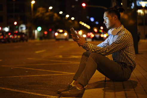 Young man sitting at roadside in the city at night using tablet - JRFF01481