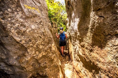 Spain, Malaga Province, El Torcal, woman hiking through gorge - SMAF00868