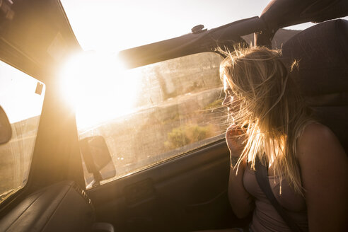 Blond woman with blowing hair sitting in car enjoying sunset - SIPF01857