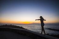 Spain, Tenerife, woman balancing on wall near the sea at sunset - SIPF01860
