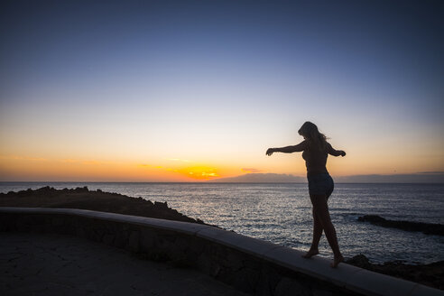 Spain, Tenerife, woman balancing on wall near the sea at sunset - SIPF01860