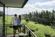 Couple standing on balcony, enjoying the landscape - SBOF00862