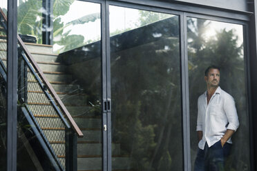 Mature man standing in his modern house, looking through window - SBOF00868