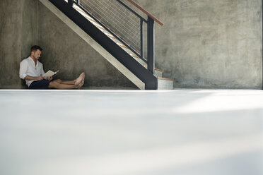 Mature man sitting under staircase, reading a book - SBOF00871