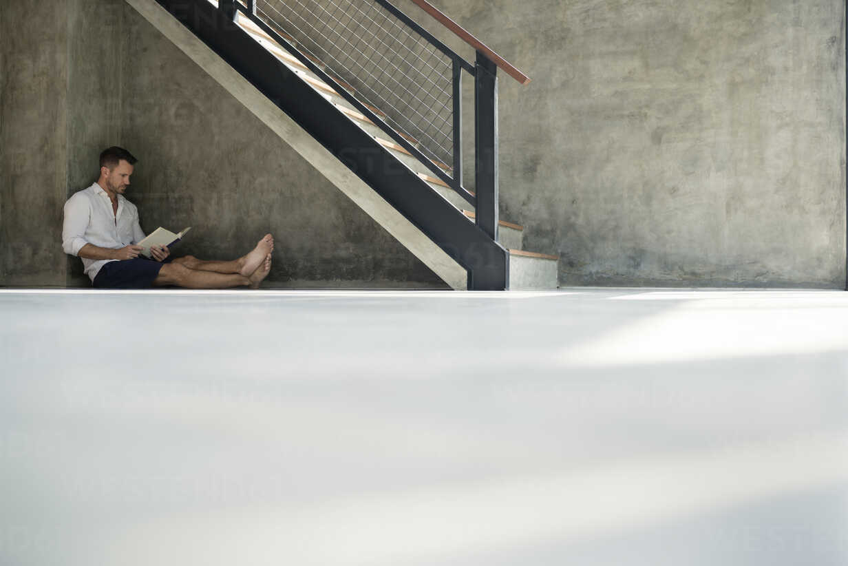 Mature man sitting under staircase, reading a book - SBOF00871 - Steve Brookland/Westend61