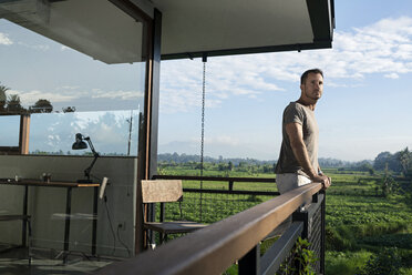 Man standing on balcony of modern house, looking at landscape - SBOF00877