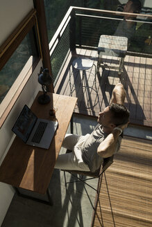 Man leaning back and taking a break from working at laptop on desk in house - SBOF00880