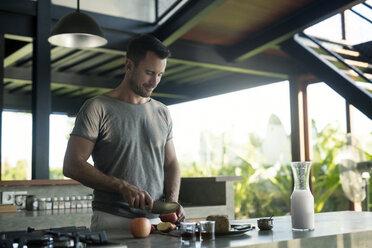 Man preparing breakdast with milk, bread and fruit - SBOF00886