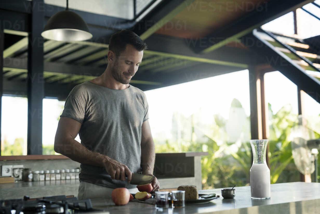 Man preparing breakdast with milk, bread and fruit - SBOF00886 - Steve Brookland/Westend61