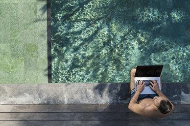 Mature man sitting at the poolside, using laptop - SBOF00898