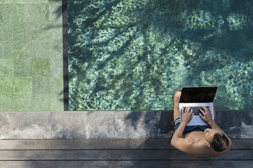 Mature man sitting at the poolside, using laptop - SBOF00898