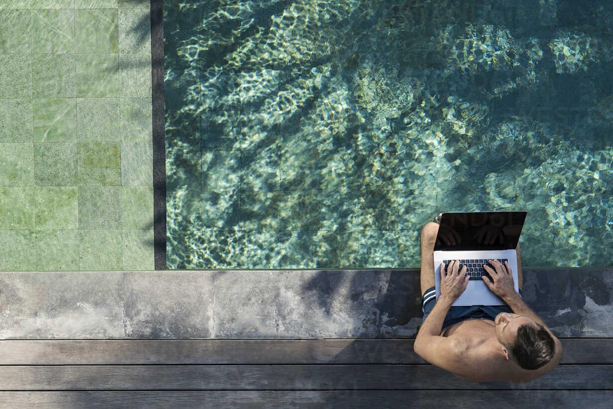 Mature man sitting at the poolside, using laptop - SBOF00898 - Steve Brookland/Westend61