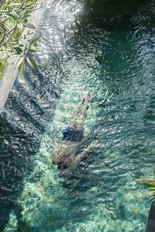 Man swimming diving under water in swimming pool - SBOF00901