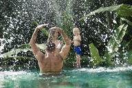 Happy family having fun , playing in swimming poo, in summer - SBOF00904