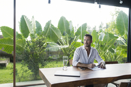 Mature man sitting at table in front of lush garden, writing - SBOF00907