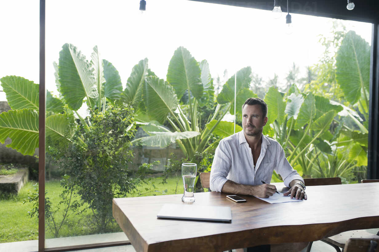 Mature man sitting at table in front of lush garden, writing - SBOF00907 - Steve Brookland/Westend61
