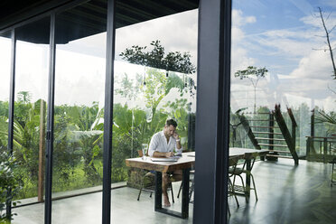 Mature man sitting at table in front of lush garden, using smartphone - SBOF00910