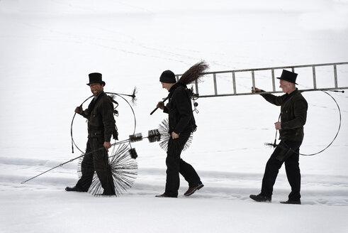 Three chimney sweeps walking in snow - LBF01701