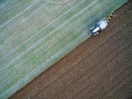 Italy, Umbria, Gubbio, Aerial view of a tractor working in the fields - LOMF00667