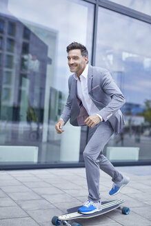 Portrait of smiling businessman skateboarding on pavement - PNEF00331