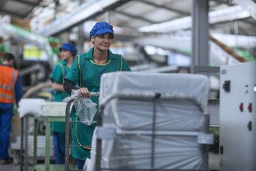 Woman pushing cart in factory - ZEF14707