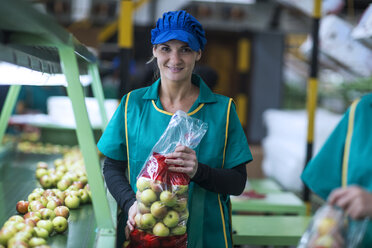 Portrait of smiling woman holding apples in plastic bags in factory - ZEF14713