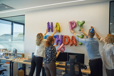 Colleagues decorating office with happy birthday writing - ZEDF00974