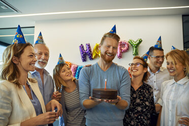 Colleagues having a birthday celebration in office with cake and party hats - ZEDF00977