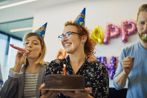 Colleagues having a birthday celebration in office with cake, party blower and party hats - ZEDF00980
