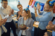 Colleagues having a birthday celebration in office with cake and party hats - ZEDF00983