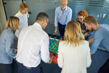 Colleagues playing foosball in office - ZEDF00986