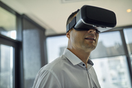 Man wearing VR glasses in office - ZEDF00992