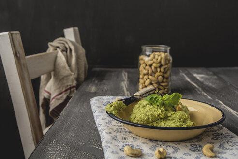 Avocado cashew spread with basil on plate, knife - ODF01571