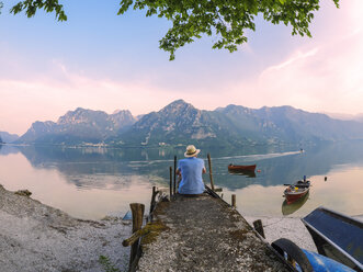 Italy, Lombardy, back view of man sitting on jetty at Lake Idro at morning twilight - LAF01948
