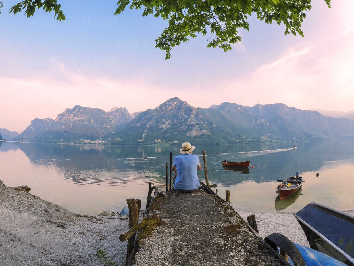 Italy, Lombardy, back view of man sitting on jetty at Lake Idro at morning twilight - LAF01948 - Albrecht Weißer/Westend61