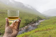 Great Britain, Scotland, Scottish Highlands, Glen Etive with River Etive and Glen Etive Falls, hand holding scotish whiskey in a glass - FOF09440