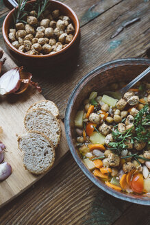 Mediterranean soup in copper pot, bowl of croutons and bread slices on wooden board - GIOF03292