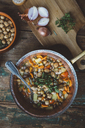 Mediterranean soup in copper pot, bowl of croutons and ingredients on wooden board - GIOF03295