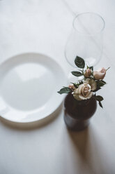 Roses in vase on laid table - GIOF03301