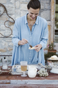Italy, laughing woman putting jam on slice of bread on terrace - ALBF00221
