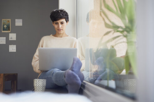 Woman at home sitting at the window using laptop - RBF06101