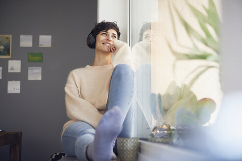 Smiling woman at home wearing headphones  sitting at the window - RBF06104