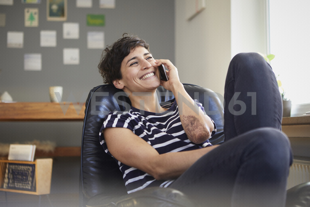 Happy woman talking on cell phone at home - RBF06116