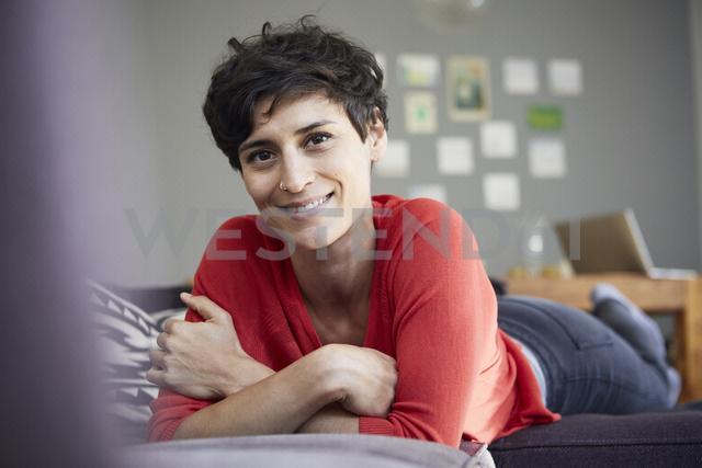 Portrait of smiling woman lying on couch at home - RBF06134