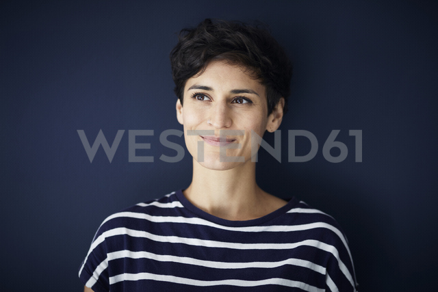 Portrait of smiling woman at blue wall - RBF06140