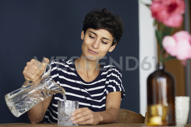 Woman at home sitting at wooden table pouring water into glass - RBF06146