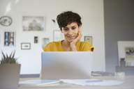 Portrait of smiling woman at home sitting at table using laptop - RBF06149
