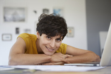 Portrait of smiling woman at home leaning on table - RBF06152