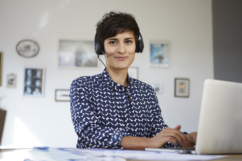 Portrait of smiling woman at home with headset and laptop - RBF06155